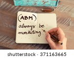 Small photo of Retro effect and toned image of a woman hand writing a note with a fountain pen on a notebook. Business acronym ABM ALWAYS BE MARKETING with handwritten text