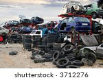 Old vehicles in a scrap yard - stock photo