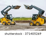 Small photo of two yellow skid steers with raiced bucket outdoors