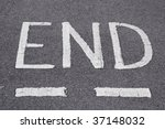 the end written in white on a road - stock photo