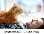 Young Man With Fluffy Cat Lyin...