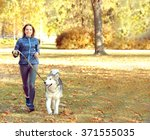 Stock photo happy young woman jogging with her dog in park 371555035