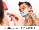 Small photo of Handsome 30 years old man shaves in front of the mirror with adjustable Double edged safety razor