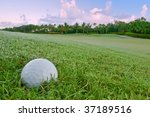golf ball lies on dewy bunker above green in morning at florida course - stock photo