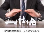Small photo of Concept of insurance with hands over a house, a car and a family