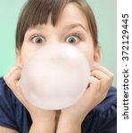 little girl is blowing big... | Shutterstock . vector #372129445