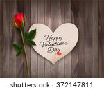 Stock vector happy valentine s day background with a note on a wooden wall and a red rose vector 372147811