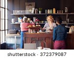 staff serving customer in busy... | Shutterstock . vector #372379087