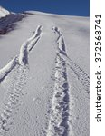 Small photo of Tracks of car stop and reverse in the snow of an alpine slope. Abstract concepts: have to stop, cannot proceed, impossible to continue, reverse, backtrack, backdown