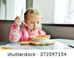 little  girl is eating in the... | Shutterstock . vector #372597154