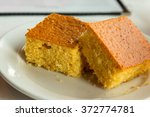 Stock photo two pieces of cornbread on a white plate 372774781