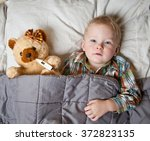 sick child boy lying in bed... | Shutterstock . vector #372823135