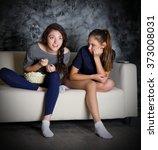 two girls looks tv at dark room | Shutterstock . vector #373008031