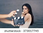 Small photo of Scared Actress Shooting Movie Scene - Young professional cinema star acting sad in a drama film
