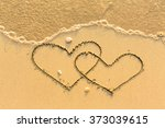 two hearts drawn on the sand of ... | Shutterstock . vector #373039615