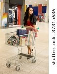 girl with  handcart stand in mall - stock photo
