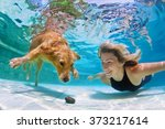 Stock photo smiley woman playing with fun and training golden retriever puppy in swimming pool jump and dive 373217614