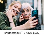 Stock photo silly young women best friends taking a selfie 373281637