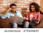 Attractive Afro-American couple pointing, talking, using laptop and tablet while sitting on beanbag chairs against brick wall