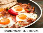 shakshuka is a dish of eggs... | Shutterstock . vector #373480921
