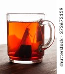 Small photo of Tea bag in glass mug on wooden table close-up macro shot, vertical