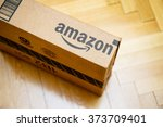 Small photo of PARIS, FRANCE - JAN 28, 2016: Amazon logotype printed on cardboard box side seen from above on a wooden parwuet floor. Amazon is an American electronic e-commerce company distribution worlwide
