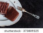 plate with cake and a fork on black background - stock photo