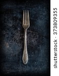antique fork on a black baking sheet - stock photo