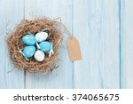 Easter Eggs In Nest Over Woode...