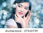 Young woman with cherry flowers. Soft blue tint. - stock photo