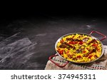 Small photo of Serving of paella al homo with spare ribs and black pudding on yellow saffron rice flavored with red bell peppers and herbs in the corner of the frame over slate with plenty of copyspace for your menu