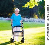 Small photo of Happy senior handicapped lady with a walking disability enjoying a walk in a sunny park pushing her walker or wheel chair, aid and support during retirement concept.