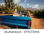 Small photo of Group of friends sitting at the back of a pick up car. Young men and women going on a road trip in nature.