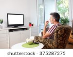 image of a young man watching tv | Shutterstock . vector #375287275