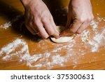 Men's Hands Knead The Dough On...
