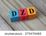 Small photo of DZD (Algerian Dinar) symbol on colorful wooden cubes