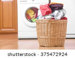 Stock photo laundry basket on the background of the washing machine 375472924