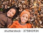 kids lying on leaves | Shutterstock . vector #375843934