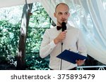 Small photo of stylish handsome emcee performing speech for toast at wedding reception