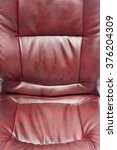 Small photo of close up upholstered office chair of claret color from artificial leather as a background