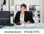 Small photo of Portrait of confident female accountant writing on documents at desk in office