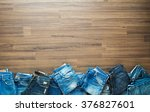 Jeans stacked on a wooden background, View from above with copy workspace