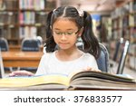 Small photo of School education and literacy concept with Asian girl kid student learning and reading book in library or classroom