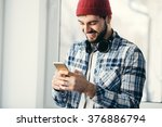 Small photo of Handsome happy hipster young man using smart phone at window. Male wearing headphones and shuffling music