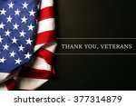 Small photo of Text Thank A You, Veterans on black background near American flag