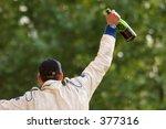 winner raising champagne above...
