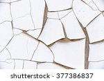Small photo of Close view of white and thick cracked paint on a weathered aluminium traffic signpost located near a highway road. A symbol of inharmonious or antagonistic to something. Abstract textured background.