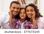 Small photo of Cute little Afro-American girl hugging her beautiful young parents. All looking at camera and smiling.