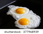 Small photo of eggs sunny side up on black greasy grill closeup