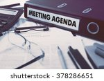 Small photo of Office folder with inscription Meeting Agenda on Office Desktop with Office Supplies. Business Concept on Blurred Background. Toned Image.